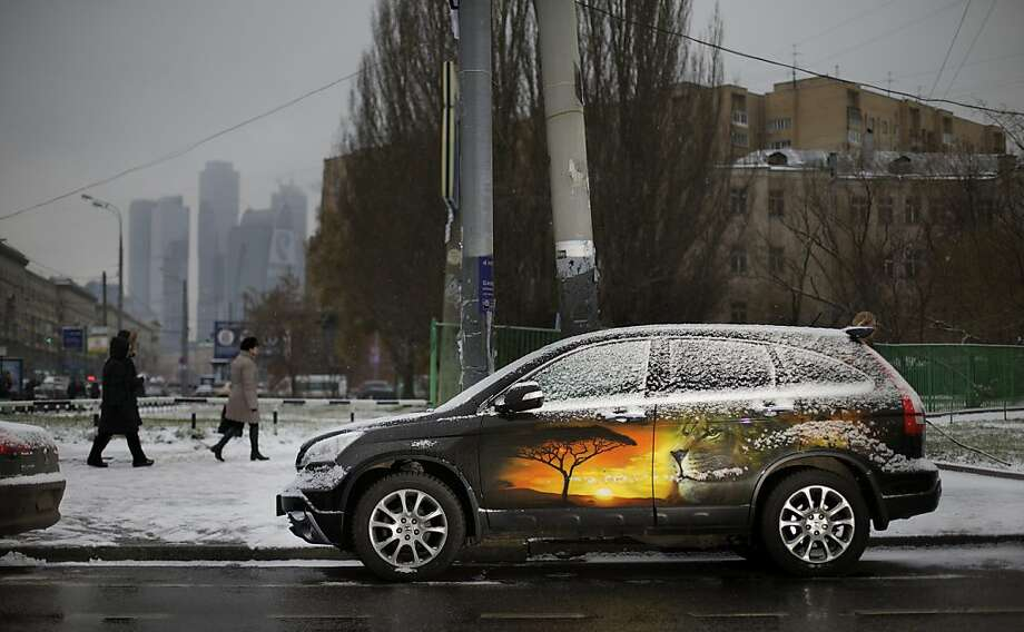 Snow on the Serengeti: A hatchback with a subtropical paint job tries to keep warm as winter comes to Moscow. Photo: Ivan Sekretarev, Associated Press