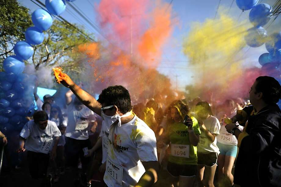 Hitting the pigment before the pavement:A runner throws paint powder at the starting line of the Kolorfest, a fundraising footrace benefiting charities in San Salvador. Photo: Jose Cabezas, AFP/Getty Images
