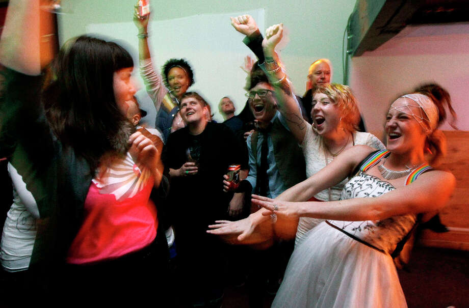 Judea Ezell, right, wearing a wedding dress, and Shena Lee, left, join other supporters of Washington state's Referendum 74, which would legalize same-sex marriage, in a celebratory dance, Tuesday, Nov. 6, 2012, at a bar in Seattle's Capitol Hill neighborhood. Photo: Ted S. Warren, AP / AP