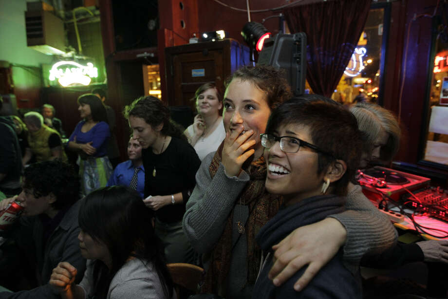 Christabel Escarez, right, and Daisy Frearson, second from right, watch early election results at the Wildrose bar in Seattle's Capitol Hill neighborhood Tuesday, Nov. 6, 2012. Both women said they were supporting Washington state's Referendum 74, which would legalize same-sex marriage. (AP Photo/Ted S. Warren) Photo: Ted S. Warren, ASSOCIATED PRESS / AP2012