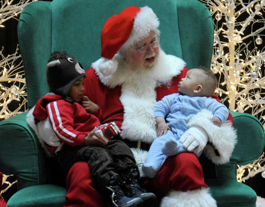 Isaac Ellis, 2, of Grosse Pointe Park, Mich., appears to not be as impressed with Santa as his brother, seven-month-old Nathan, inside the Compuware Building during  Christmas Wonderfest at Campus Martius Park in Detroit on Sunday, Nov. 25, 2012. The outdoor event featured a shopping area, carriage rides, ice skating and Santa Claus. (AP Photo/Detroit News, Elizabeth Conley) Photo: Elizabeth Conley, Associated Press / The Detroit News
