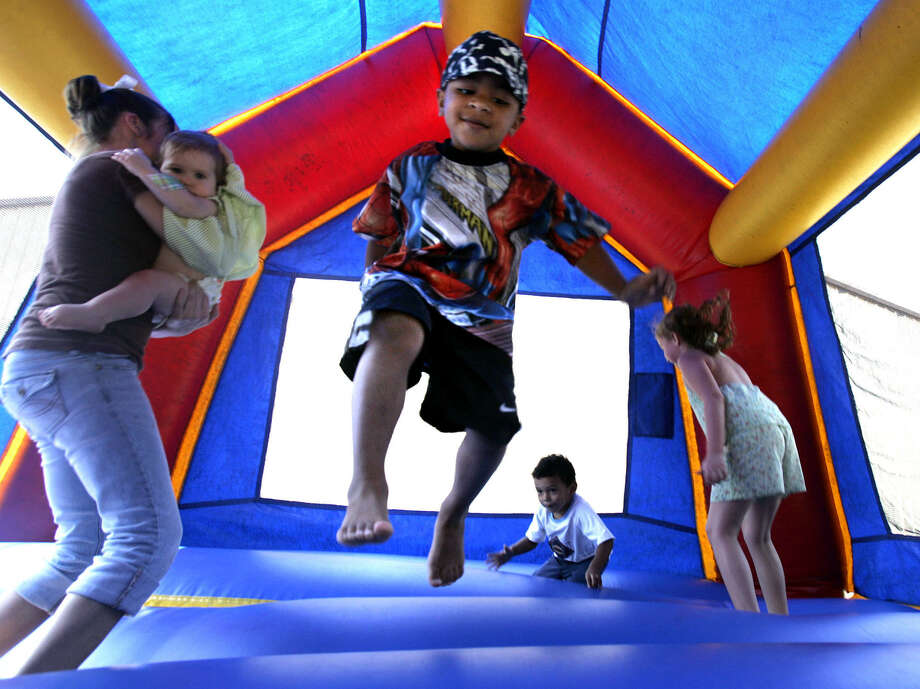 In this Sept. 11, 2005 file photo, children play in a bounce house in Vidor, Texas. A nationwide study released Monday, Nov. 26, 2012, found inflatable bounce houses can be dangerous and the number of kids injured in related accidents has soared 15-fold in recent years. The numbers suggest 30 U.S. children a day are treated in emergency rooms for broken bones, sprains, cuts and concussions from bounce house accidents. (AP Photo/LM Otero, File) Photo: AP, STF / AP