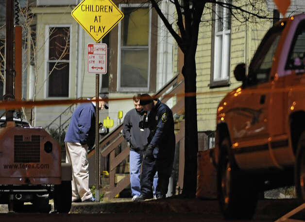 Police look for evidence outside of 157 Myrtle Ave. (house on right) where police confirmed one person is dead and two others were injured after an attack at 2:30 pm on Monday, Nov. 26, 2012 in Albany, N.Y.  (Lori Van Buren / Times Union) Photo: Lori Van Buren