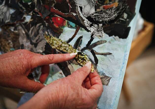 "Angi Shine adds touches to one of the ""paintings"" made from pieces torn by hand from pages of The Chronicle. Photo: Russell Yip, The Chronicle"