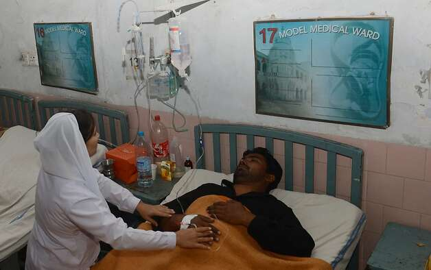 A Pakistani paramedic staff gives medical treatment to a patient who fell ill after drinking a toxic cough syrup at a hospital in Lahore. Photo: Arif Ali, AFP/Getty Images