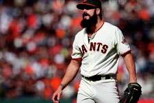 Giants closer Brian Wilson watches as Atlanta players cross home plate in the tenth inning Sunday.