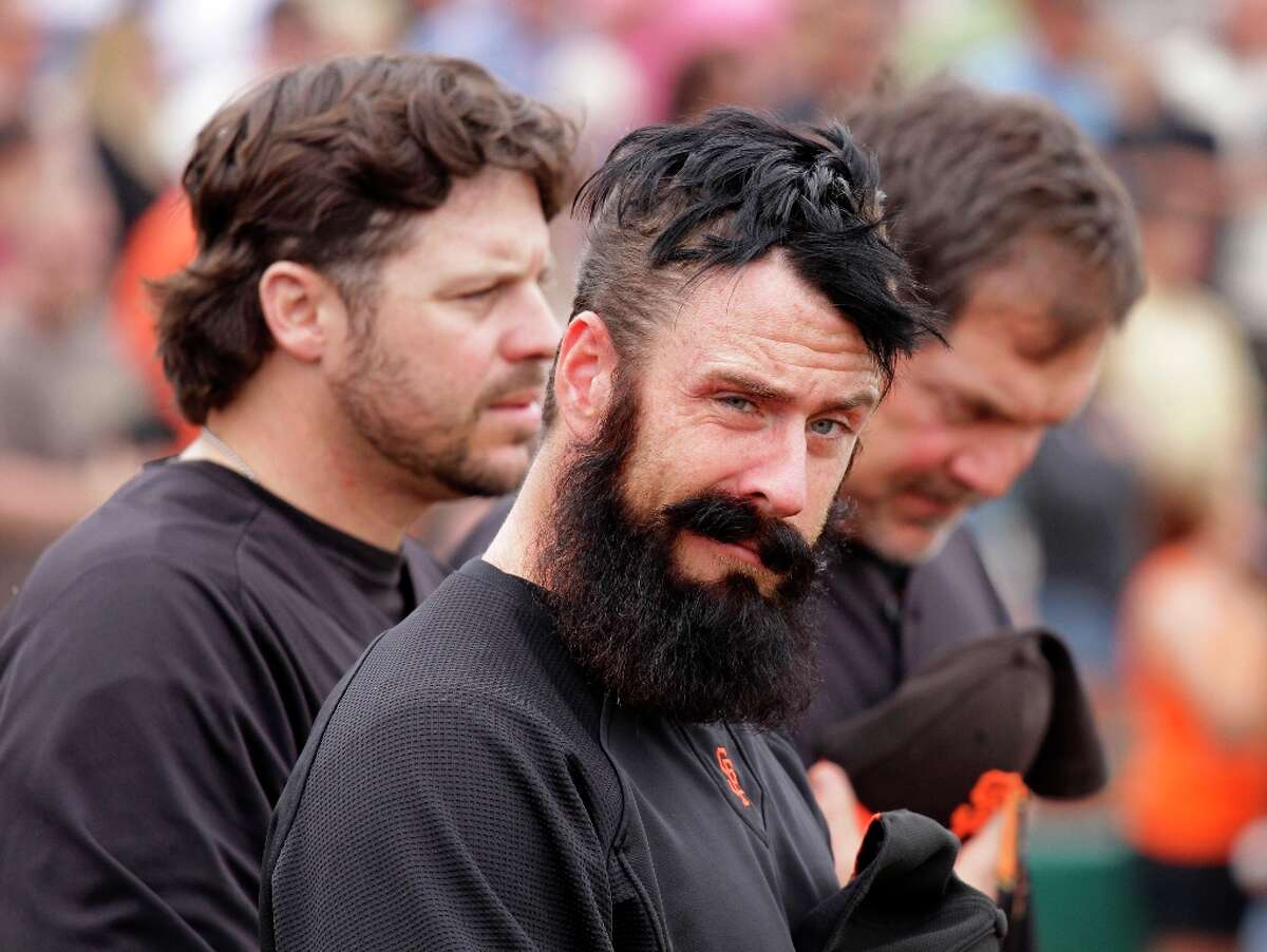San Francisco Giants relief pitcher Brian Wilson, center, stands between spring instructor Ryan Klesko, left, and manager Bruce Bochy, right, while listening to the national anthem before their spring training baseball game against the Oakland Athletics in Scottsdale, Ariz., Sunday, March 20, 2011. Wilson was recently injured with a strained rib cage muscle and is uncertain for opening day.