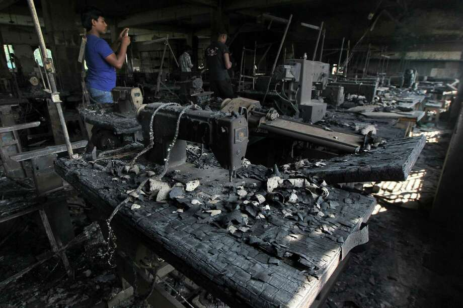 A man takes photographs inside a garment-factory where a fire killed more than 110 people Saturday  on the outskirts of Dhaka, Bangladesh, Monday, Nov. 26, 2012. Bangladeshi workers protested blocks from the gutted fire Monday, demanding justice for the victims and improved safety. Some 200 factories were closed for the day after the protest erupted in Savar, a suburb of Dhaka, the capital.  (AP Photo) Photo: STR / AP