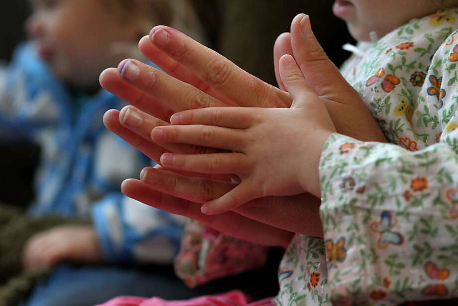 Teacher Jackie Thurman holds Hailey Lee as they clap during the morning welcome song,  Monday November 26, 2012,  at the Sunset Co-op Nursery School in San Francisco, Calif. The preschoolers at the co-op, learn by playing instead of memorization. Photo: Lacy Atkins, The Chronicle