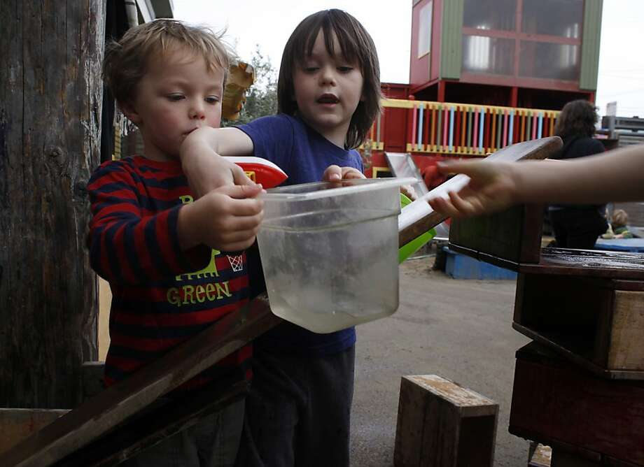 Sean Fannon, left and Billy Nicholson fetche water to make a slide in the yard at the Sunset Co-op Nursery School,  Monday November 26, 2012, in the outer sunset district of San Francisco, Calif. Photo: Lacy Atkins, The Chronicle