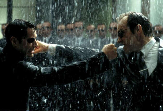 """In the """"Matrix"""" films, the intelligent machines have taken over, turning humans into an energy source and keeping them docile in a computer simulation of the world as it was in 1999, the year the first movie in the franchise came out. The main computer enforcer within this virtual world is Agent Smith (Hugo Weaving), right, shown fighting human hero Neo, played by Keanu Reeves. Photo: Warner Bros. Pictures / SL"""