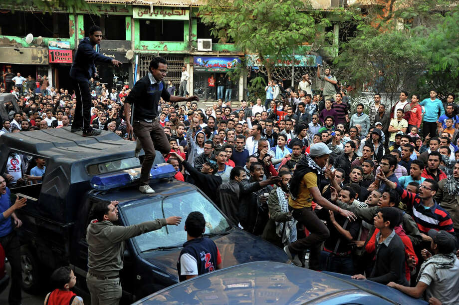Egyptians stand on police vehicles on Monday during the Cairo funeral of a protestor who was wounded by security forces last week and died Sunday. Photo: Hussein Tallal, STR / AP