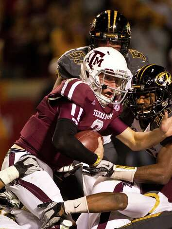 Texas A&M quarterback Johnny Manziel (2) looks to see if he crossed the plane as the Missouri defense tries to  stop him during the fourth quarter of a NCAA football game, Saturday, Nov. 24, 2012, in Kyle Field in College Station.  ( Nick de la Torre / Houston Chronicle ) Photo: Nick De La Torre, Staff / © 2012  Houston Chronicle