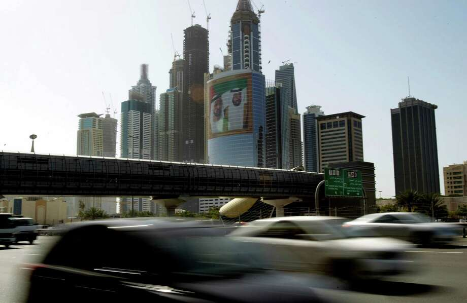 FILE - This March 9, 2011, file photo, shows a large image of Sheik Mohammed bin Rashid Al-Maktoum, UAE Prime Minister and ruler of Dubai, rear left, and Sheik Khalifa bin Zayed Al-Nahyan, UAE President, right, on a tower at Internet City, as cars pass drive on Sheikh Zayed's highway in Dubai, United Arab Emirates. An upcoming U.N. gathering that will seek agreements on Internet oversight is raising alarms from a broad coalition of critics including the U.S. government, tech giants such as Google and rights groups concerned that changes could lead to greater efforts to filter the Web and stifle innovation for cyberspace. (AP Photo/Kamran Jebreili, File) Photo: Kamran Jebreili
