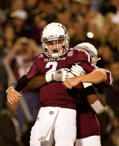 Texas A&M quarterback Johnny Manziel (2) is bear hugged by Texas A&M offensive linesman Jarvis Harrison (51) after Manziel ran for a touchdown during the third quarter of a NCAA football game against Missouri, Saturday, Nov. 24, 2012, in Kyle Field in College Station.  ( Nick de la Torre / Houston Chronicle ) Photo: Nick De La Torre, Staff / © 2012  Houston Chronicle