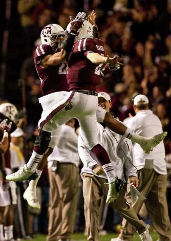 Texas A&M defensive back Dustin Harris (22) and Texas A&M quarterback Johnny Manziel (2) celebrate after Manziel threw a touchdown pass during the second quarter of a NCAA football game, Saturday, Nov. 24, 2012, in Kyle Field in College Station.  ( Nick de la Torre / Houston Chronicle ) Photo: Nick De La Torre, Staff / © 2012  Houston Chronicle