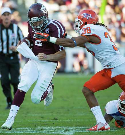 Texas A&M quarterback Johnny Manziel (2)  runs past Sam Houston State defensive back Darnell Taylor (38) during the first half of a college football game at Kyle Field, Saturday, Nov. 17, 2012, in College Station. ( Smiley N. Pool / Houston Chronicle ) Photo: Smiley N. Pool, Staff / © 2012  Houston Chronicle