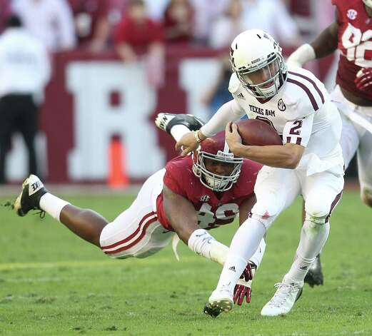 Texas A&M quarterback Johnny Manziel (2) evades the tackle of Alabama defensive lineman Ed Stinson (49) during the second quarter of a college football game at Bryant-Denny Stadium, Saturday, Nov. 10, 2012, in Tuscaloosa.  ( Karen Warren / Houston Chronicle ) Photo: Karen Warren, Staff / © 2012  Houston Chronicle