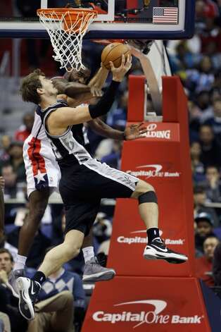 The Spurs' Tiago Splitter (22) is fouled by Martell Webster (9) of the Wizards on Monday in Washington.  (Rob Carr / Getty Images)