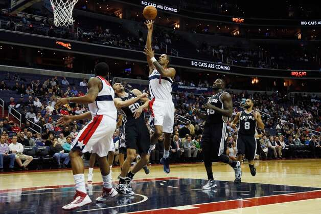 The Wizards' Trevor Ariza (1) puts up a shot over the Spurs' Manu Ginobili on Monday in Washington. (Rob Carr / Getty Images)