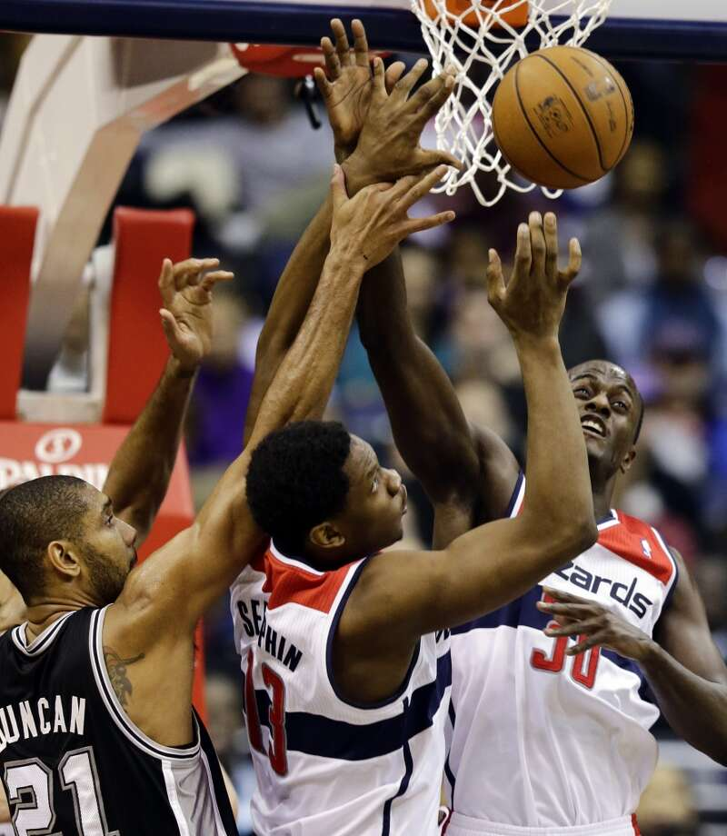 Spurs forward Tim Duncan, and Wizards forward Kevin Seraphin and center Earl Barron go for the rebound  on Monday in Washington. (Alex Brandon / Associated Press)
