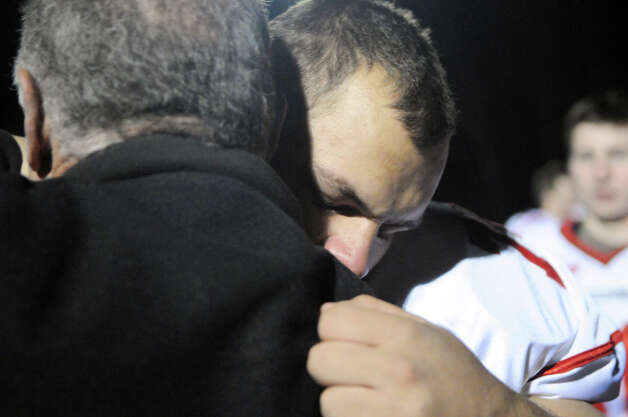 "Coach Rich Albonizio hugs player Nick Spano as the Greenwich High School football team holds its annual ""Burning of the Shoes"" ceremony at the school in Greenwich, Conn., Nov. 26, 2012. The tradition is meant to symbolize the transition of seniors out of the football program, burning their shoes demonstrates that their shoes can never be filled. Photo: Keelin Daly / Stamford Advocate Riverbend Stamford, CT"