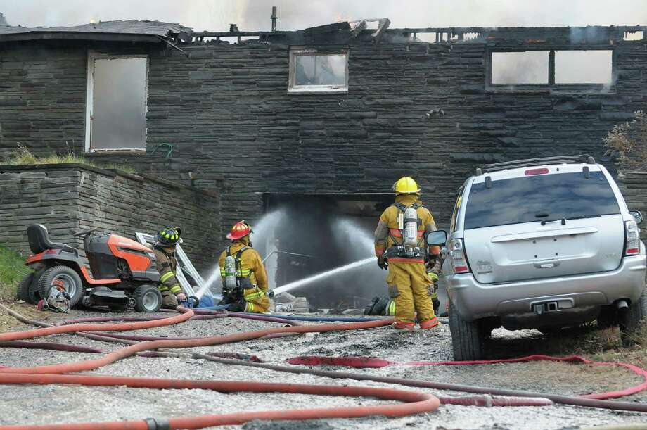 Firefighters spray water into the garage as they battle a house fire on Garfield Road on Monday, Nov. 26, 2012 in Eagle Mills, N.Y.  (Paul Buckowski / Times Union) Photo: Paul Buckowski