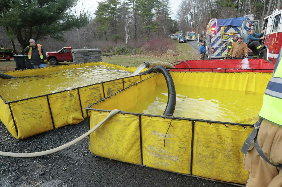 Water is pumped into large holding tanks and then pumped up a hill as crews battled a house fire on Garfield Road on Monday, Nov. 26, 2012 in Eagle Mills, N.Y. Because of a lack of water at the scene, water had to be trucked in. (Paul Buckowski / Times Union)