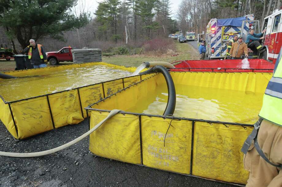 Water is pumped into large holding tanks and then pumped up a hill as crews battled a house fire on Garfield Road on Monday, Nov. 26, 2012 in Eagle Mills, N.Y.   Because of a lack of water at the scene, water had to be trucked in.   (Paul Buckowski / Times Union) Photo: Paul Buckowski