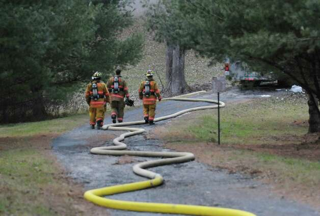 Firefighters walk up the long driveway along side a water hose to help battle a house fire on Garfield Road on Monday, Nov. 26, 2012 in Eagle Mills, N.Y. Because of a lack of water at the scene, water had to be trucked in and then pumped up the hill to the home.  (Paul Buckowski / Times Union) Photo: Paul Buckowski