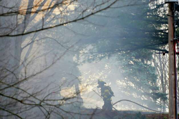 A firefighter pulls up a hose as he battled a house fire on Garfield Road on Monday, Nov. 26, 2012 in Eagle Mills, N.Y.   Because of a lack of water at the scene, water had to be trucked in and then pumped up the hill to the home.   (Paul Buckowski / Times Union) Photo: Paul Buckowski