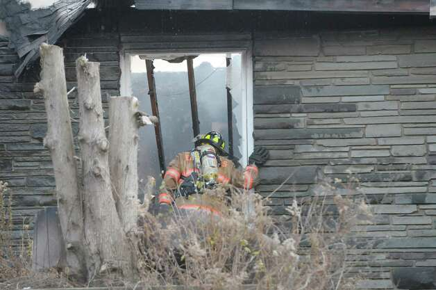 A firefighter looks inside the structure as crews battled a house fire on Garfield Road on Monday, Nov. 26, 2012 in Eagle Mills, N.Y.  (Paul Buckowski / Times Union) Photo: Paul Buckowski
