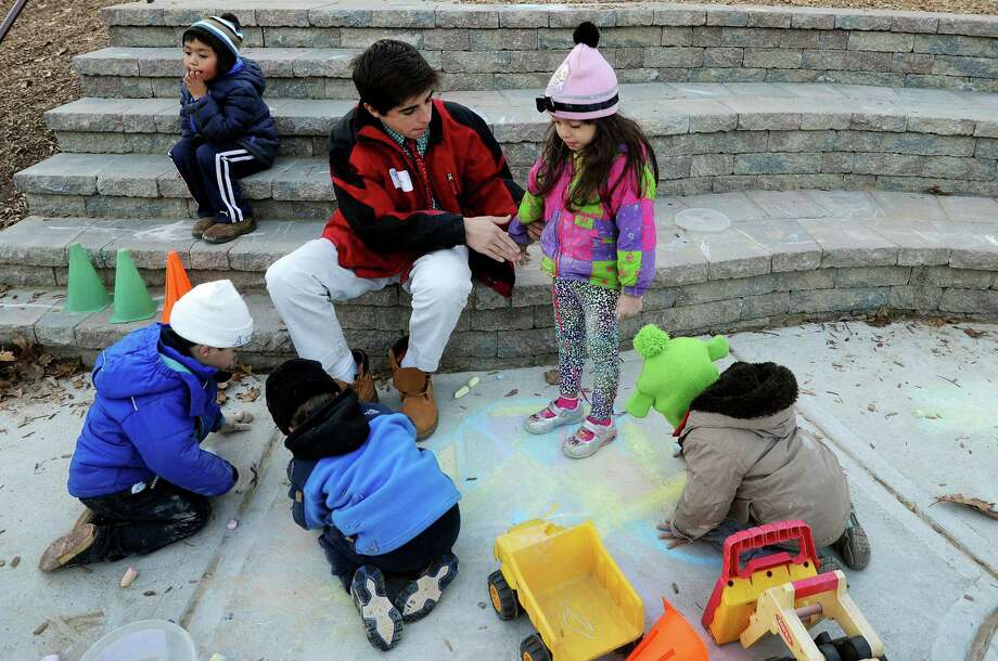 "Brunswick student volunteer Thomas Errichett wipes chalk off the jacket of Julie Campos at Family Centers Arch Street Preschool in Greenwich, Conn. on Monday Nov. 26, 2012. On November 27, residents, companies and charities across the country are celebrating ""Giving Tuesday,"" an inaugural national day of service, urging folks to spend the day giving back to their community. Photo: Cathy Zuraw / Greenwich Time"