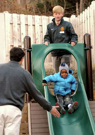 "Brunswick student volunteers Michael Marzonie and Gus Fraser help Devin Stencil go down the slide at Family Centers Arch Street Preschool in Greenwich, Conn. on Monday Nov. 26, 2012. On November 27, residents, companies and charities across the country are celebrating ""Giving Tuesday,"" an inaugural national day of service, urging folks to spend the day giving back to their community. Photo: Cathy Zuraw / Greenwich Time"