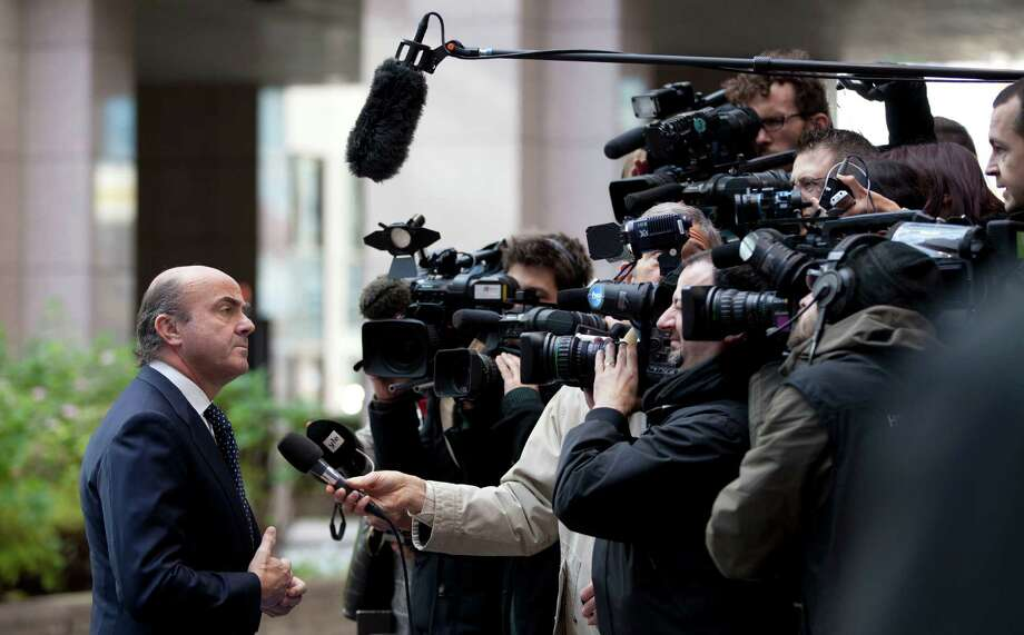 Spain's economy minister, Luis de Guindos, speaks with reporters as he arrives Monday for a meeting of European finance ministers in Brussels. Photo: Virginia Mayo, STF / AP