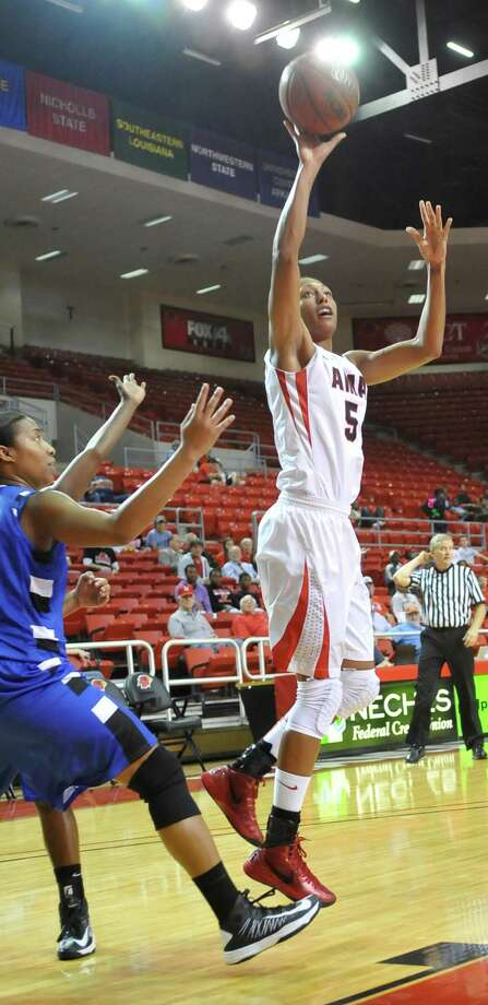 Lady Cardinal #5, Kalis Loyd, right, fights her way past Saints defender #52, Alisha Crump, left, to score two points.   The Lamar University Lady Cardinals hosted the Our Lady of the Lake Saints Monday night at the Montagne Center.      Dave Ryan/The Enterprise Photo: Dave Ryan