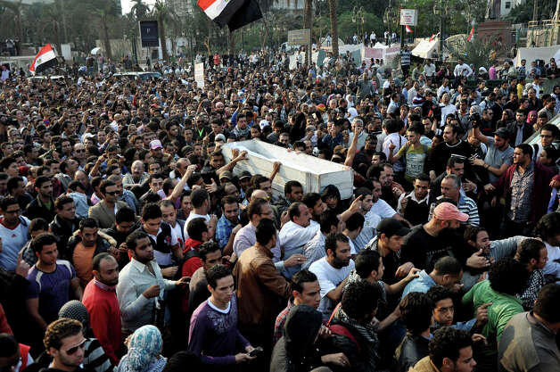 Egyptians carry the body of Gaber Salah, who was who was killed during clashes with security forces in Cairo, Egypt, Monday, Nov. 26, 2012. Thousands of Egyptians on Monday gathered into Cairo's Tahrir Square to attend the funeral of Salah, who was severely injured during clashes with security forces last week and died Sunday night. (AP Photo/Hussein Tallal) Photo: Hussein Tallal