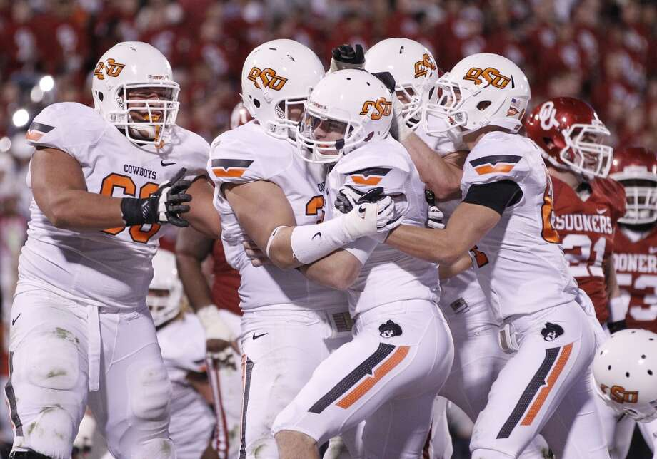 Buffalo Wild Wings: Oklahoma State (Big 12 No. 4) vs. Michigan State (Big Ten No. 4/5)  -- Oklahoma State quarterback J.W. Walsh (center) is congratulated by teammates after touchdown against Oklahoma.  (Sue Ogrocki / Associated Press)