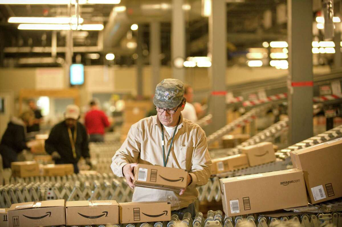 In this file photo, an Amazon.com employee grabs boxes off the conveyor belt to load in a truck at their Fernley, Nev., warehouse. Cyber Monday, coined in 2005 by a shopping trade group that noticed a spike in online sales on the Monday after Thanksgiving when people returned to their work computers, is the next in a line of days that stores are counting on to jumpstart the holiday shopping season. This year it is expected to be the biggest online shopping day of the year for the third year in a row.