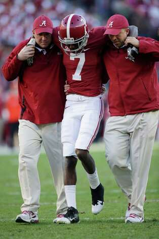 Alabama wide receiver Kenny Bell (7) is helped from the field after being injured during the first half of an NCAA college football game against rival Auburn at Bryant-Denny Stadium in Tuscaloosa, Ala., Saturday, Nov. 24, 2012. No. 2 Alabama has few big problems going into the SEC championship game against Georgia this Saturday, but the Crimson Tide is starting to run low on wide receivers.  Bell is the third lost for the season to injury. (AP Photo/Dave Martin) Photo: Dave Martin