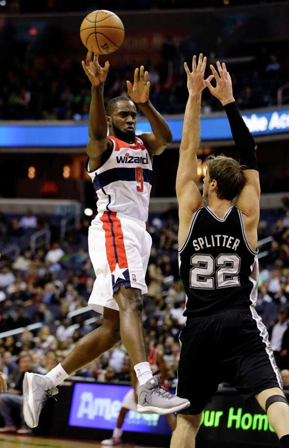 Washington Wizards forward Martell Webster passes the ball in front of San Antonio Spurs forward Tiago Splitter, from Brazil, in the first half of an NBA basketball game Monday, Nov. 26, 2012, in Washington.(AP Photo/Alex Brandon) Photo: Alex Brandon