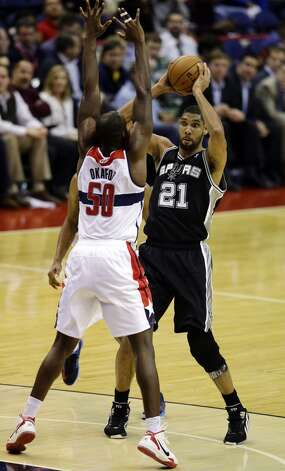 San Antonio Spurs forward Tim Duncan holds the ball as he is guarded by Washington Wizards center Emeka Okafor in the second half of an NBA basketball game Monday, Nov. 26, 2012, in Washington. The Spurs won 118-92. The Wizards are now 0-12. (AP Photo/Alex Brandon) (Associated Press)