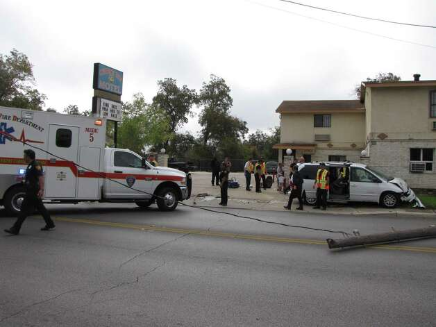 A minivan went crashing into a pole on Monday, Nov. 26, 2012, at the intersection of Commerce Street and New Braunfels Avenue. Neither the driver nor her four young children were seriously hurt in the crash, but the impact split the utility pole and caused it to land on the street along with electrical wires. Photo: Ana Ley,  San Antonio Express-News
