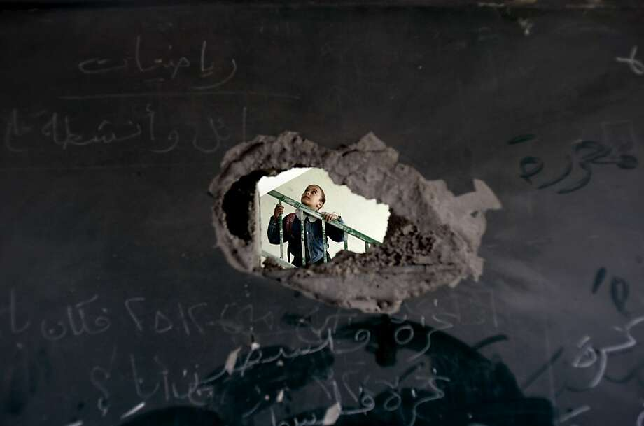 A Palestinian schoolgirl is seen through a hole in a blackboard days after an Israeli strike hit a school in Gaza City, Monday, Nov. 26, 2012. Israel launched its offensive on Nov. 14 in a bid to halt months of Palestinian rocket attacks. It says it inflicted heavy damage on Gaza militants, but the territory's armed groups fired hundreds of rockets into Israel before a cease-fire was declared Wednesday, Nov. 21, 2012. Photo: Adel Hana, Associated Press