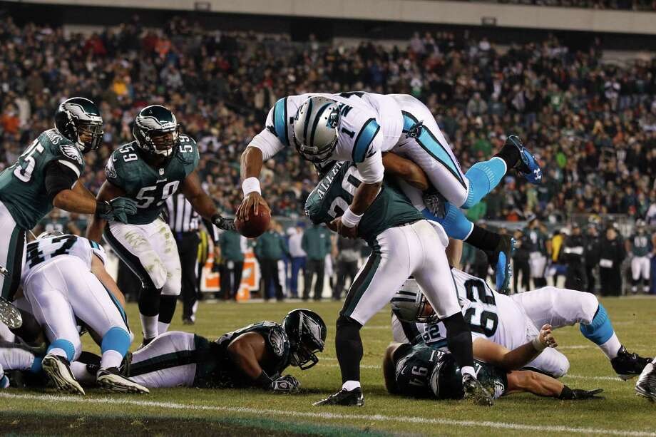 Panthers quarterback Cam Newton, top, hurdles Eagles safety Nate Allen to score one of his two rushing touchdowns Monday night. Photo: Mel Evans, STF / AP