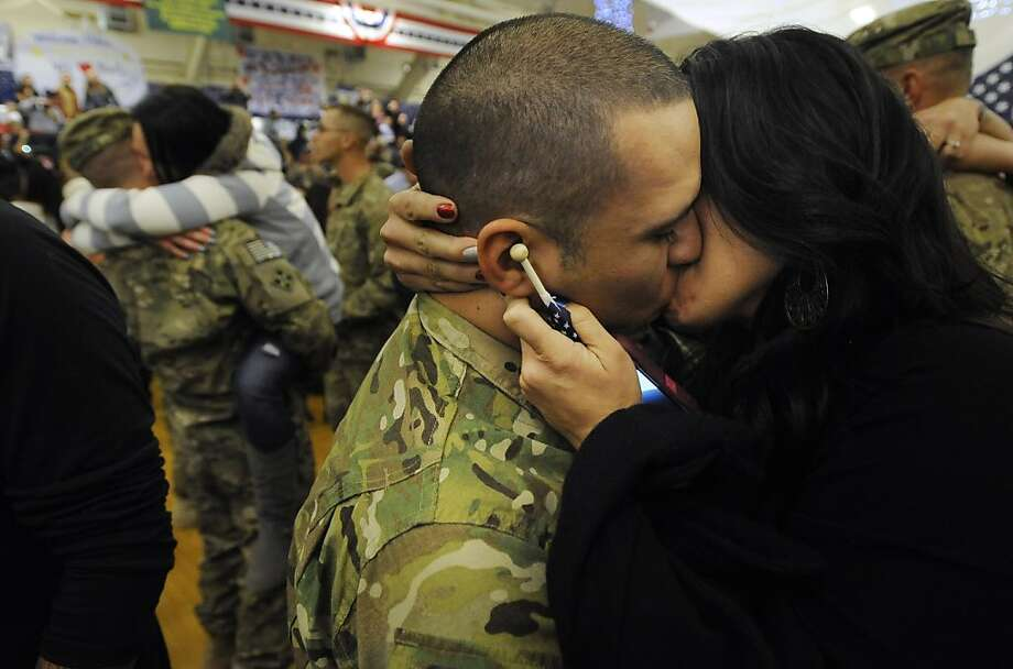 Cassandra Castro, right, gives a welcome-home kiss to her husband, Spc. Phillip Castro at Fort Carson, Colo. Monday, Nov. 26, 2012, at a welcome home ceremony for soldiers with Fort Carson's 4th Brigade Combat Team, 4th Infantry Division. The soldiers were deployed in Afghanistan in support of Operation Enduring Freedom. Photo: Mark Reis, Associated Press