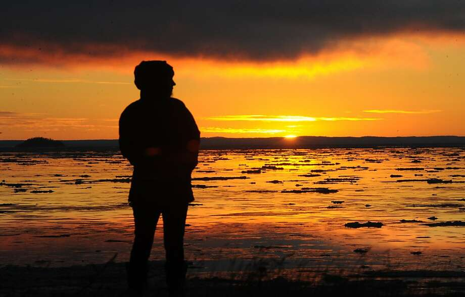 Andrea Cummings watches the sunset as floes pass in the Turnagain Arm  on Sunday afternoon, Nov. 25, 2012, in Anchorage, Alaska. Photo: Bill Roth, Associated Press