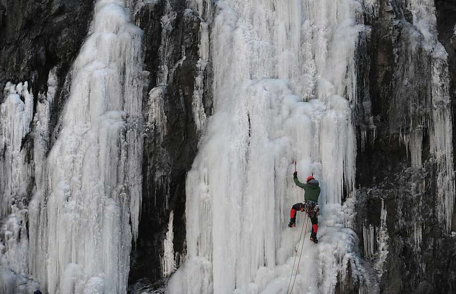 Pickin' and grinnin': Chris Williams climbs a wall of ice along the Seward Highway just south of Anchorage after sunset. Photo: Bill Roth, Associated Press