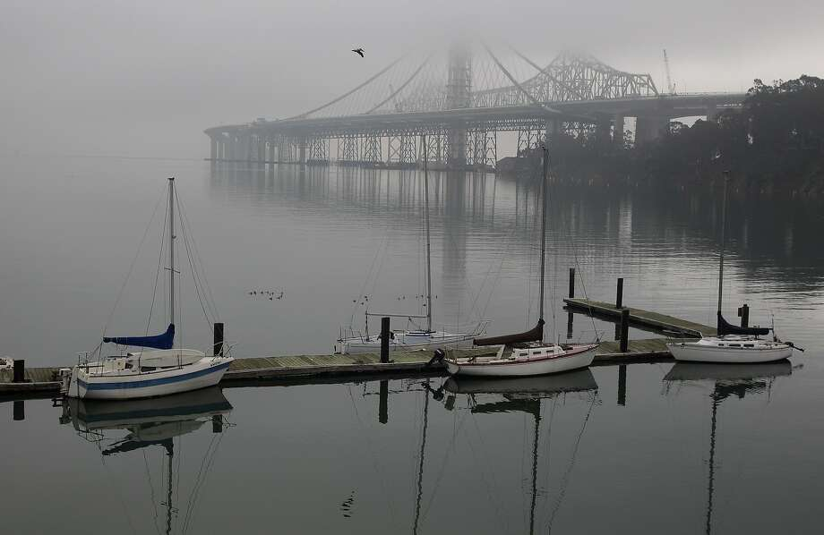 Fog engulfs the eastern span of the Oakland-San Francisco Bay Bridge, which is under construction, Monday, Nov. 26, 2012, seen from Clipper Cove on Treasure Island in San Francisco. A heavy fog has allowed only 27 planes per hour to enter or leave San Francisco International airport, with delays of up to two hours. Photo: Ben Margot, Associated Press