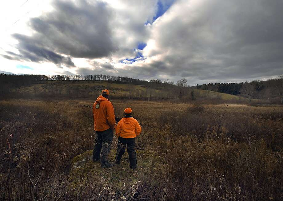 """I haven't seen many out today"" said hunter Ted Cady Jr., left, with his son Hunter, 10, of Bridgewater Township, Pa. as they hunt in a field on Monday, Nov. 26, 2012 in Brooklyn Township, Pa., during the first day of deer season using a rifle. Photo: Butch Comegys, Associated Press"